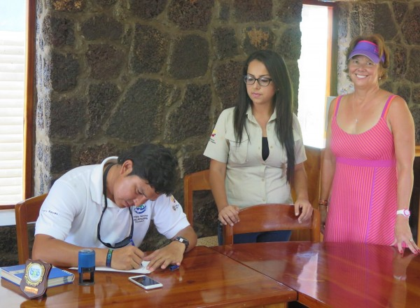 Harry Reyes, director of conservation and restoration of marine ecosystems, signs Chapter Two's logbook for Janet Hayes